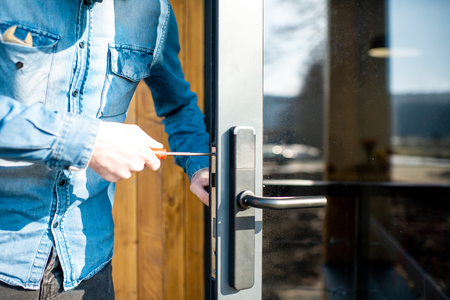 Man repairing door lock of the entrance glass door, close-up view with no face