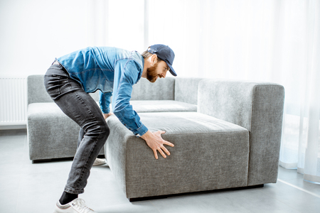 Courier or handyman in blue shirt and cap mounting a new couch in the apartment Stock Photo