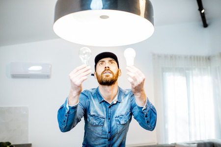 Handyman choosing between energy save and cheap incandescent lamp while changing light in the appartment 免版税图像