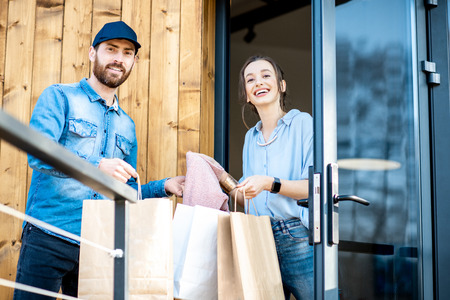Delivery man bringing some goods packaged in paper bags for a young woman client to home. Buying clothes online and delivery concept Stock Photo