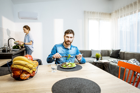Man eating healthy salad in the living room of the modern apartment with woman washing dishes on the background