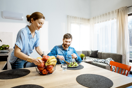 Happy man and woman during the dinning time with healthy food in the living room of the modern apartment