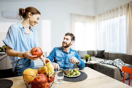 Happy man and woman during the dinning time with healthy food in the living room of the modern apartment, wide angle view