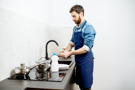 Handsome man in apron doing household chores washing dishes on the kitchen at home