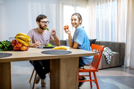 Young man and woman enjoying healthy vegan food sitting at the dinning table full of fruits and vegetables in the modern apartment
