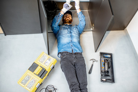 Handyman repairing kitchen plumbing lying under the sink on the floor, view from above Banque d'images - 118140264