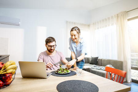Young couple using laptop during the dinning time with healthy salad in the living room of the modern apartment