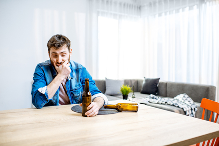 Drunk male alcoholic sitting with bottles feeling depressed and suffering from head ache at home