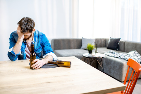 Drunk male alcoholic sitting with bottles feeling depressed and suffering from head ache at home Stock Photo - 118140340