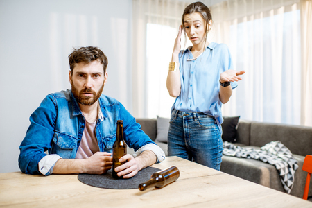 Drunk man suffering from alcoholism feeling depressed sitting at home with young woman in despair on the background