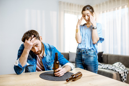 Drunk man suffering from alcoholism feeling depressed sitting at home with young woman in despair on the background Stockfoto - 118140355