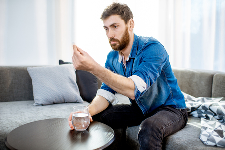 Man drinking some medicines feeling bad or having hangover after the alcohol party, sitting on the couch at home