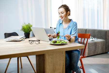 Young woman having a snack with healthy salad while working with laptop at home