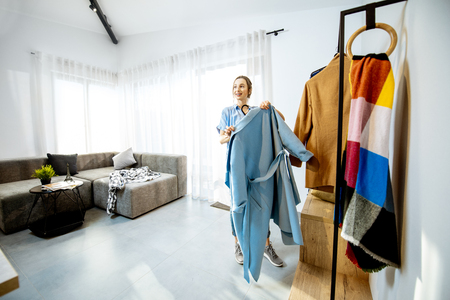 Young stylish woman wearing blue coat standing in the living room of the beautiful bright apartment