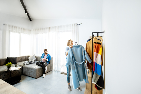 Young stylish woman wearing blue coat standing in the living room with man sitting the couch in the beautiful bright apartment Stock Photo