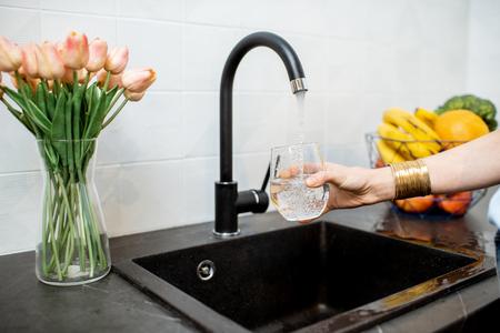 Vrouw vult glas met kraanwater om in de keuken te drinken Stockfoto