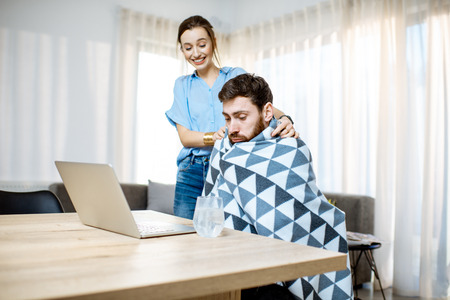 Young woman taking care giving some medicine for a man feeling sick covered with blanket at home