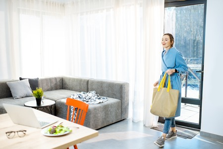 Young stylish woman in blue coat coming home with shopping back, entering the door of the modern apartment Stock Photo