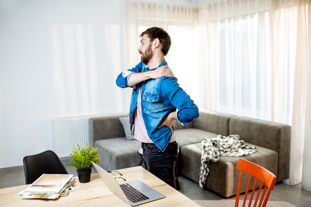 Man suffering from acute back pain while standing up from the working place at home