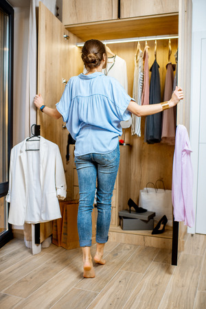 Young woman choosing clothes to wear, standing in the wardrobe at home Banco de Imagens