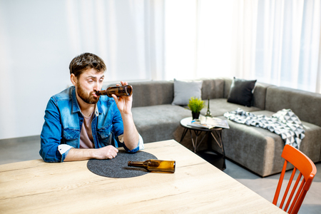 Drunk male alcoholic sitting with bottles feeling depressed and suffering from head ache at home Stock Photo - 118140513