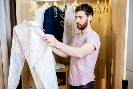 Handsome man choosing shirt to wear standing in the wardrobe at home
