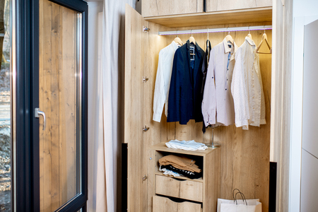Wooden wardrobe with elegant male clothes at home Banco de Imagens