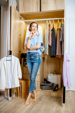 Full length portrait of a young beautiful woman standing near the wardrobe full of clothes