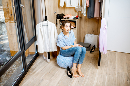 Portrait of a young woman sitting in the wardrobe full of clothes at home Stock Photo