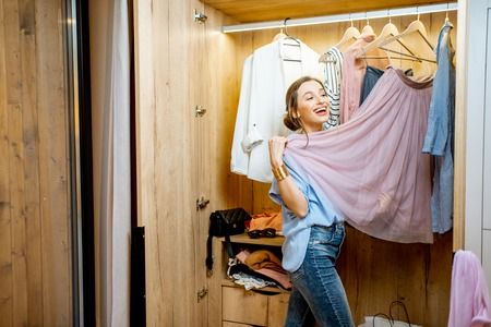 Young and happy woman choosing clothes to wear in the wardrobe at home