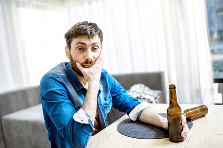 Portrait of a drunk male alcoholic sitting with bottles feeling depressed and suffering from head ache at home Stock Photo - 118140592