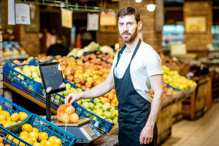 Portrait of a handsome worker weghing apples on the scales in the supermarket