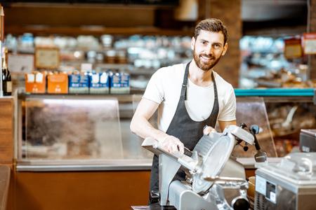 Ritratto di un bel lavoratore in uniforme che affetta il formaggio con una macchina da taglio al supermercato