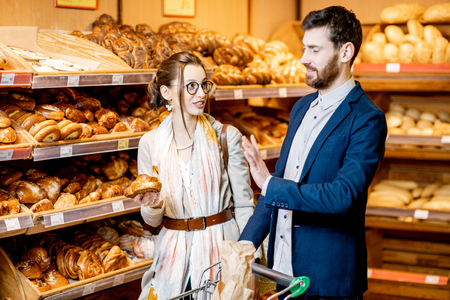 Young and happy couple choosing fresh pastries, standing together with shopping cart in the bakery department of the supermarket Banco de Imagens