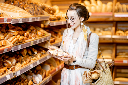 Young and elegant woman choosing sweet pastry, standing with bag in the bakery department of the supermarket