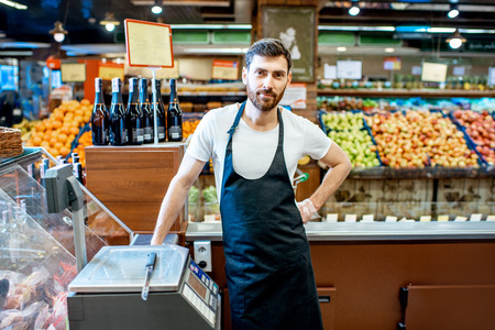 Portrait of a handsome seller or shop worker in apron standing at the counter in the supermarket Фото со стока