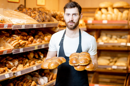 Portrait of a handsome baker in uniform standing with fresh pastries in the bakery deparment of the supermarket Banco de Imagens