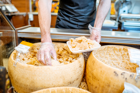 Man packing parmesan into the trail selling cheese in the shop, close-up view with no face
