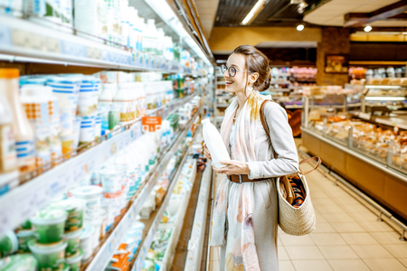 Young woman choosing milk standing near the shelves with dairy products in the supermarket