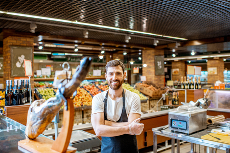 Portrait of a handsome seller standing at the counter with jamon in the supermarket 写真素材