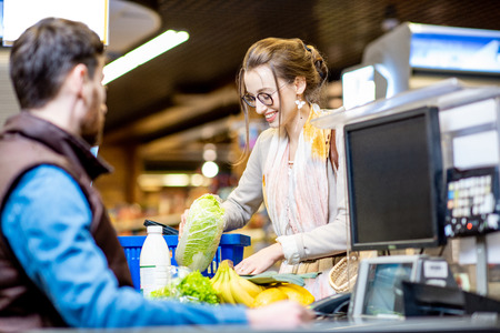 Young and cheerful woman putting products on the cash register buying food in the supermarket Stock Photo