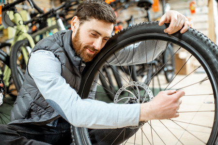 Portrait of a handsome man as a buyer or salesperson with bicycle wheel at the bicycle shop