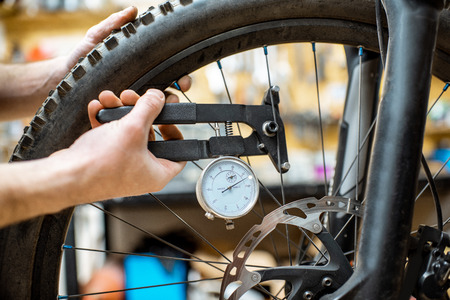 Man aligning a bicycle wheel, checking the needles stretch with special tool at the working place, close-up view
