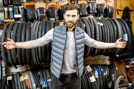 Portrait of a handsome salesman or shop owner standing with bicycle tires in the sports store
