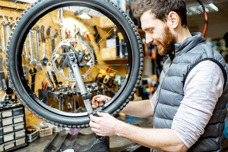 Man aligning bicycle wheel tensing spokes with a special key at the working place of the workshop Stockfoto