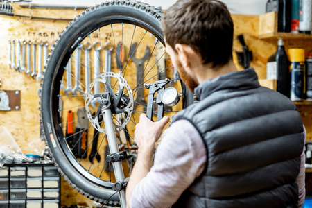 Man aligning a bicycle wheel, checking the needles stretch with special tool at the working place