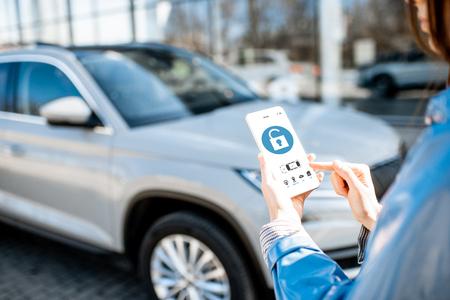 Frau, die das Auto mit der mobilen Anwendung auf einem Smartphone entsperrt. Konzept der Fernbedienung und des Autoschutzes über das Internet