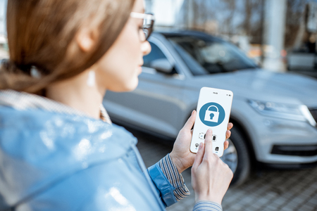 Woman locking car using mobile application on a smart phone. Concept of remote control and car protection through the internet Stock Photo