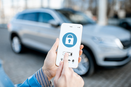 Locking car using mobile application on a smart phone. Concept of remote control and car protection through the internet 版權商用圖片 - 119987399