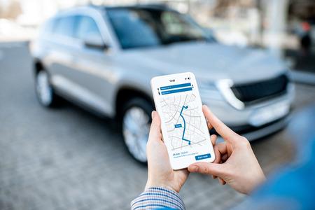 Frau mit Smartphone mit Navigations-App, Nahaufnahme mit modernem Auto im Hintergrund Standard-Bild